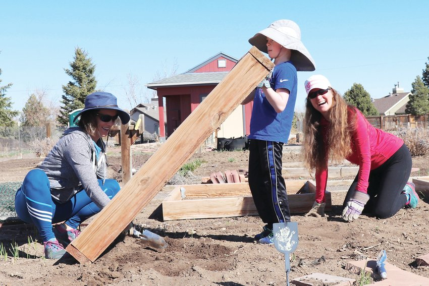 As this year's gardening season gets underway, Erin Newton, left, Grayson Inman and Laura Bennett put together a plot at the Rose Roots Community Garden, 12920 W. 84th Ave.