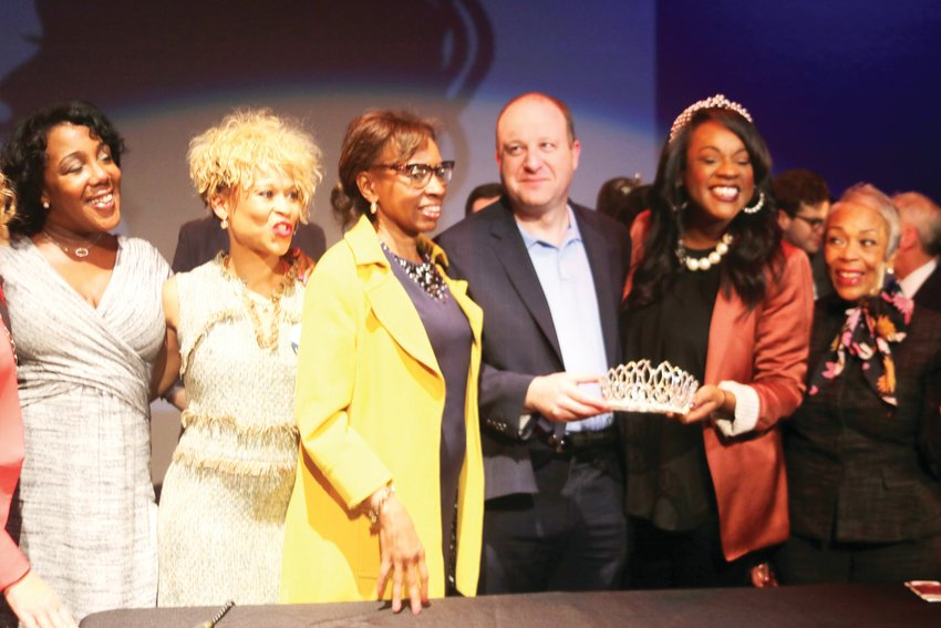 A couple of people on the CROWN Coalition join, from left, Sen. Rhonda Fields, D-Aurora, who is standing next to Colorado Gov. Jared Polis; Rep. Leslie Herod, D-Denver; and Rep. Janet Buckner, D-Aurora, on the far right, for a bill signing celebration on March 6 at the Cleo Parker Robinson Dance theater in Denver.