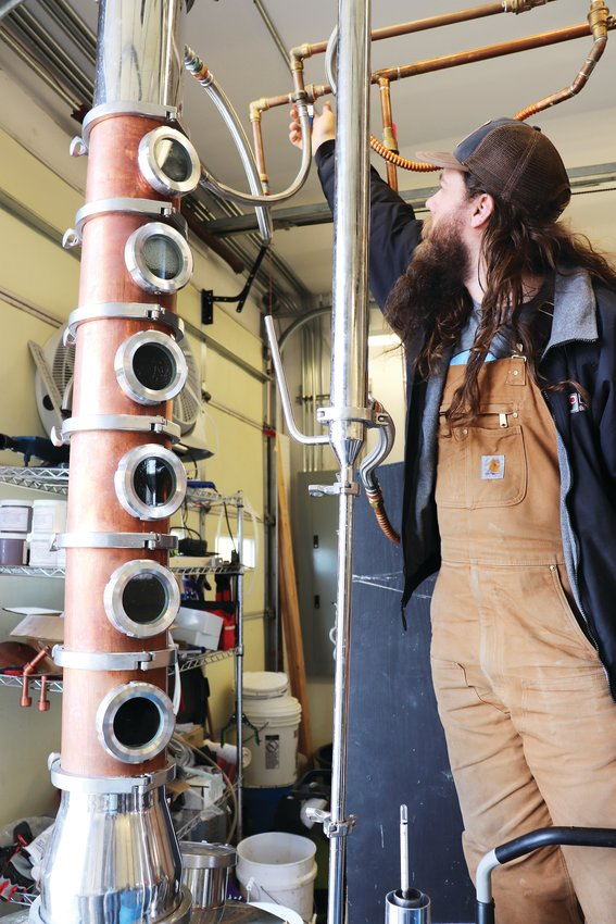 "Austin Adamson, co-owner and distiller at Lakewood distillery Ballmer Peak, adjusts the equipment that distills ethanol to be made into hand sanitizer. ""This is an effort to get more hand sanitizer to the people who want it and calm some of the panic,"" Adamson said."