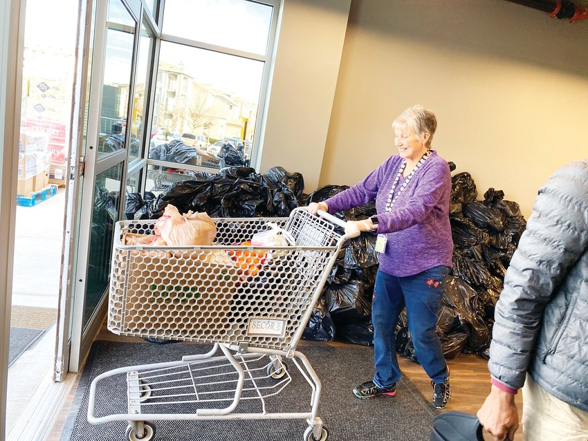 Roxanne Sheppard wheels out a cart of food, enough for one family, to be packed into the trunk of one of the dozens of cars lined up at SECOR offices March 25.