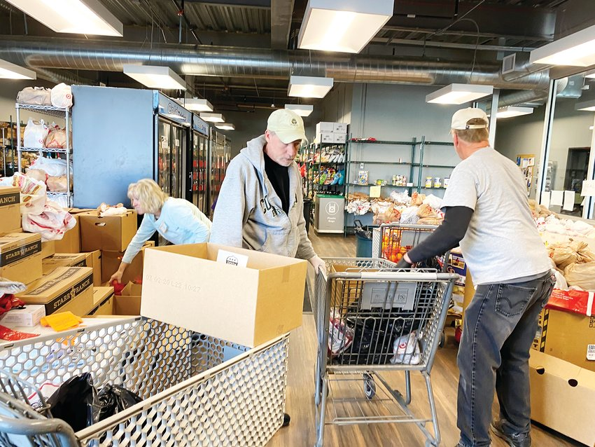 Volunteers pack bags of food items, about enough to feed a family of four for a week, into shopping carts to be wheeled out to people waiting in their cars.