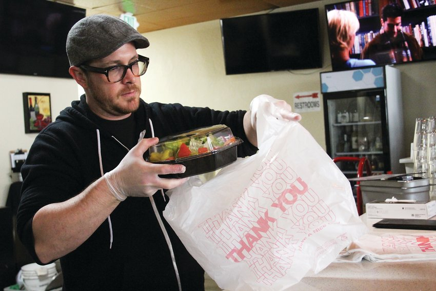 Brian Meadows, co-owner of Gallo Italian Supper Club and Bake, bags up a to go order. Meadows said the restaurant is bringing in a quarter of its average sales.