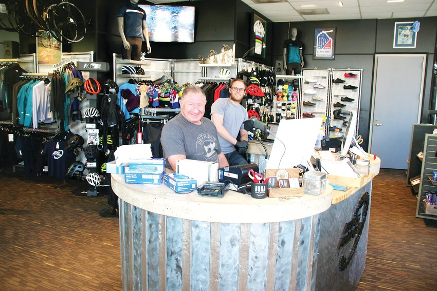 Big Ring Cycles owner Seth Wolins and bike service professional Phil Dixon inside the shop on March 26.
