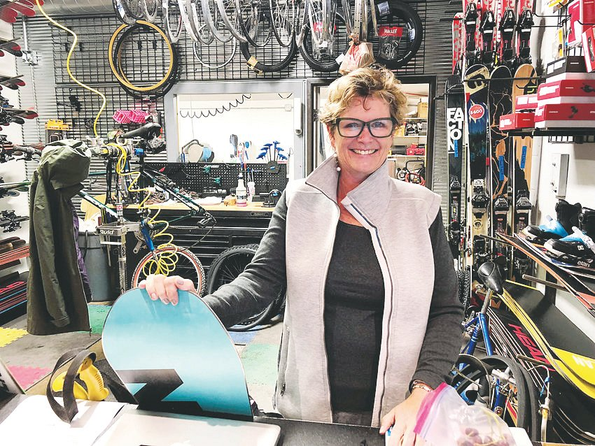 K.C. Neel stands inside the bike and ski shop she and her husband run in downtown Castle Rock. The couple recently commissioned a mural spanning the length of their building.