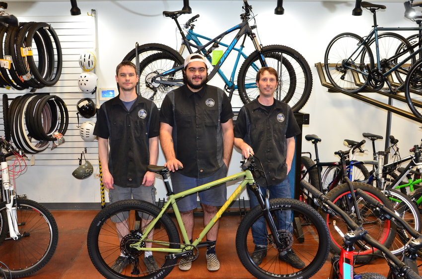 "From left, Alex Rewun, 40; Paul Rodriguez, 26; and Brian Shuey, 37, the three owners and managers of The Bicycle Shack in Arvada, stand April 7 at their shop. Colorado's stay-at-home order deemed a long list of industries ""critical"" — meaning employees in those sectors can still come to work — and bicycle repair shops are on that list."