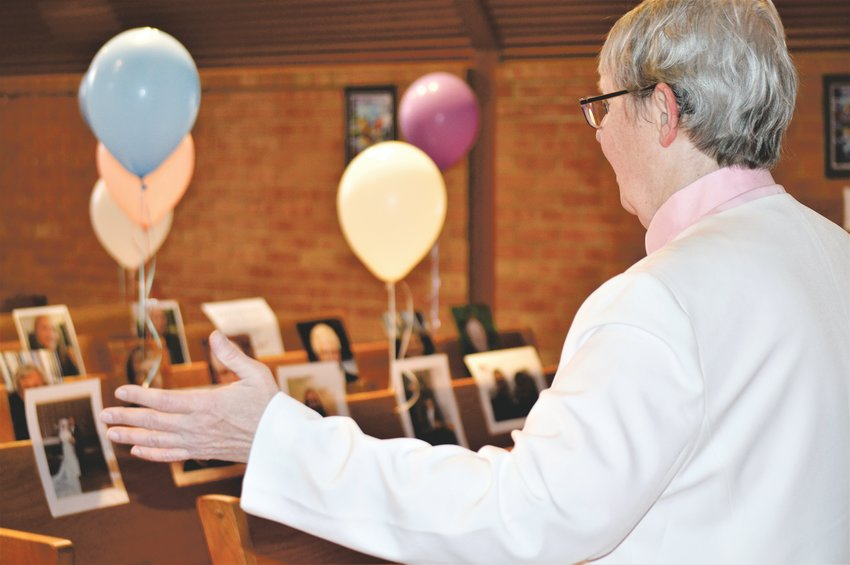 Pastor Barb Martens of  Advent Lutheran Church in Westminster takes in the balloons and photographs members of the congregation left in their places in the church's pews before Easter Sunday service, which was shown via a live Facebook stream.