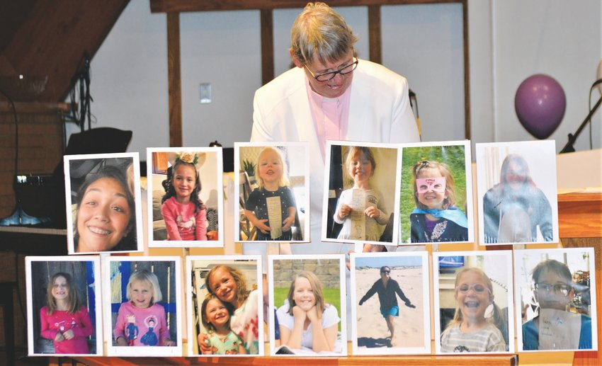 Pastor Barb Martens of Westminster's Advent Lutheran Church looks at a collection of photographs of the children in her congregation she collected for the church's Easter Sunday service. The virtual service was streamed to the congregation via Facebook.