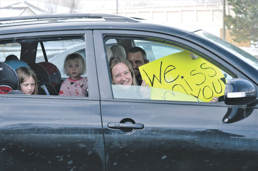 The Beach Family, Nyssa and Ryan in the front seat and Hannah, 6, and Maddie 4, wait in their warm car outside of Advent Lutheran Church in Westminster for a glimpse of Pastor Barb Martens Easter Sunday. An handful of the church's congregation pulled into the church's parking lot honk horns, flash their lights and wave signs to greet the pastor.