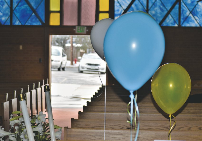 Balloons, candles and stained glass frame the door to the parking lot at Westminster's Advent Lutheran Church. Like churches across the country, Advent Lutheran is closed to visitors but the clergy have been streaming services live to Facebook since the COVID-19 quarantines began. For Easter Sunday, members of the church filled the pews with their photographs and balloons, gathering in their cars in the lot outside to greet the clergy.