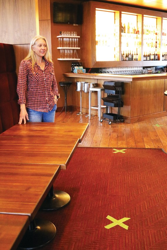 Co-owner Delinda Fatianow stands inside one of the Indulge Bistro and Wine Bar Highlands Ranch locations April 1. The x's on the floor, which are 6 feet apart, indicate where the store's customers can stand as they pick up grocery items.