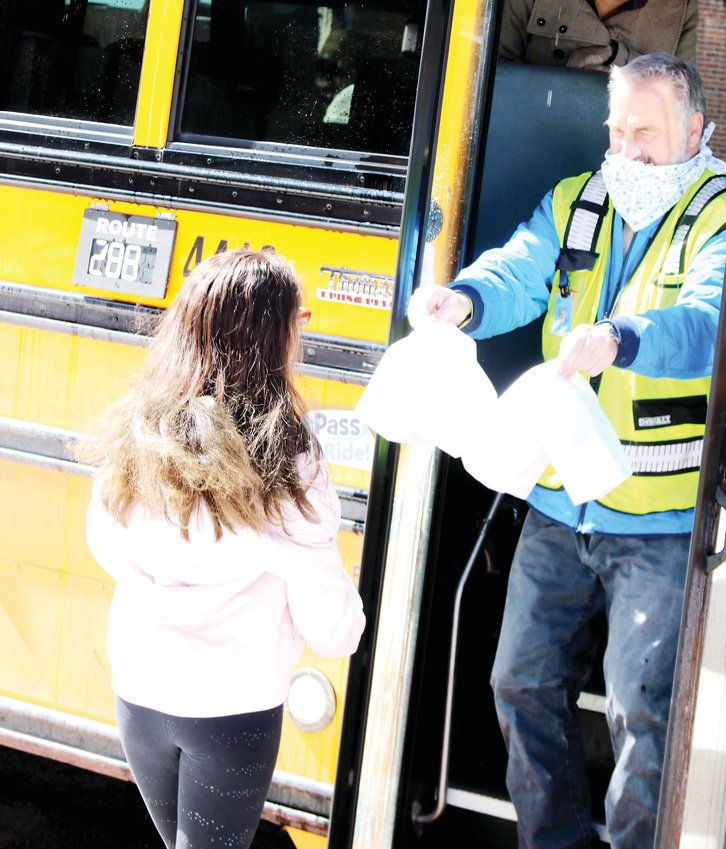 Greg Morris, a school bus driver with Denver Public Schools, provides sacked breakfast-and-lunch meals to a student on April 14. The school district launched the program to be able to provide meals to students and families during school closure because of the COVID-19 pandemic.
