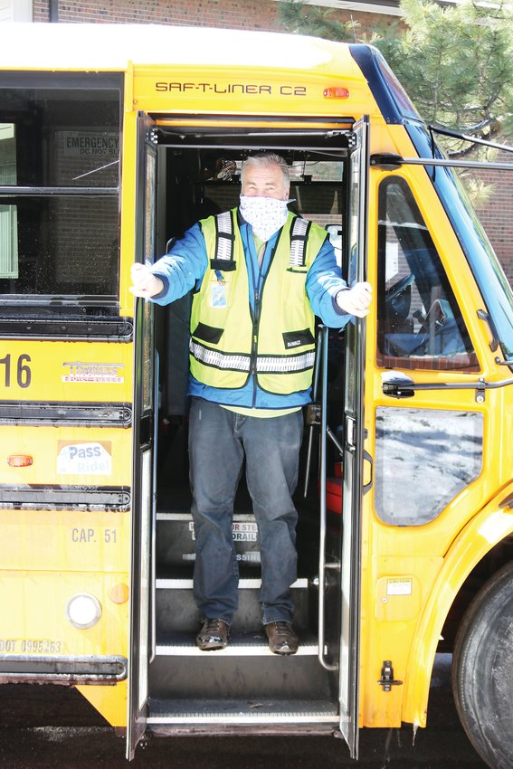 Greg Morris, a school bus driver with Denver Public Schools, opens the doors to his bus to deliver food on April 14 to students learning from home during COVID-19 pandemic.