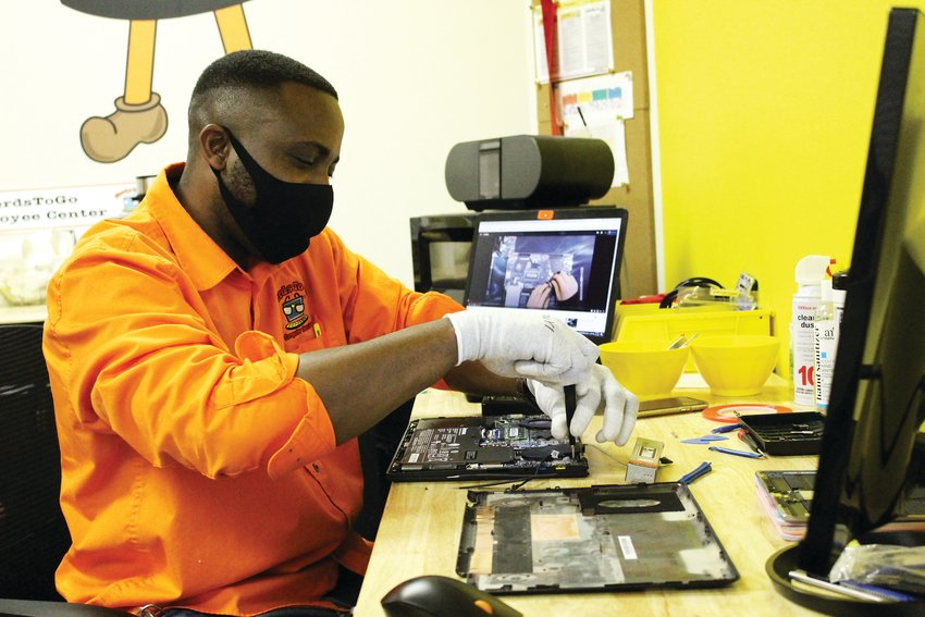 NerdsToGo technician Dre Ennis fixes a laptop at the IT office in Parker April 15.