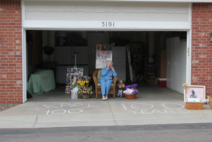 Evelyn Berkey sat in a chair in her garage surrounded by flowers and cards to celebrate her 100th birthday. Friends and family planned to surprise her with a caravan so loved ones could drive bast and wishe her a happy birthday.