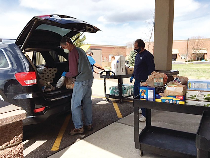 Instead of having guests come inside to get food from the Parker Task Force, volunteers are loading up their cars with the items they need while wearing masks and gloves.