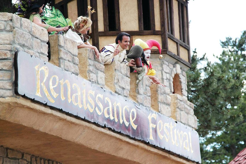 Entertainers greet people from above as they pass through the gates of the Colorado Renaissance Festival castle in July 2019.