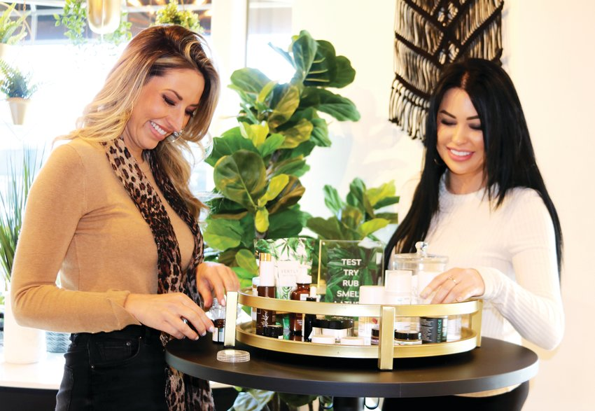 Samantha Bowers and Jessica Kiley organize one of The CBD Suite's testing tables, which contains topicals such as lotions, balms and pain cream. The shop's other testing table includes consumable products, such as tinctures and gummies.