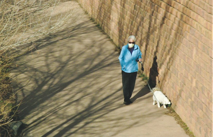 A woman wears a mask while she walks her dog along the Clear Creek trail in Golden.