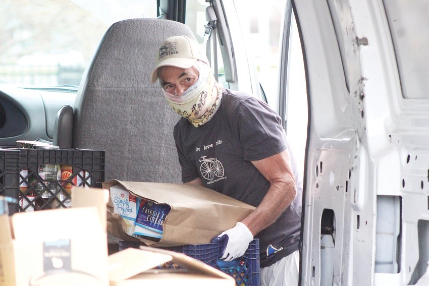 Peter Rockwood, a volunteer for the Action Center, loads food up into a van. The Action Center partnered with Mile Hi Church to host food drives on April 28 and April 30.