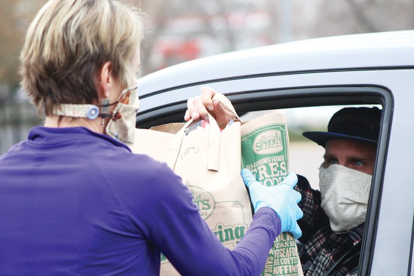 Brad Conner hands Monnie Biety a bag of food. The food drive didn't require residents to get out of their cars, and all volunteers from both entities wore masks, as recommended by the state.