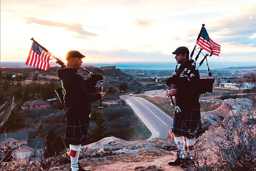 Jake Auten, firefighter/paramedic, and Lt. Jay Allen of the Castle Rock Fire Department play their bagpipes with the Rock monument in the backdrop.