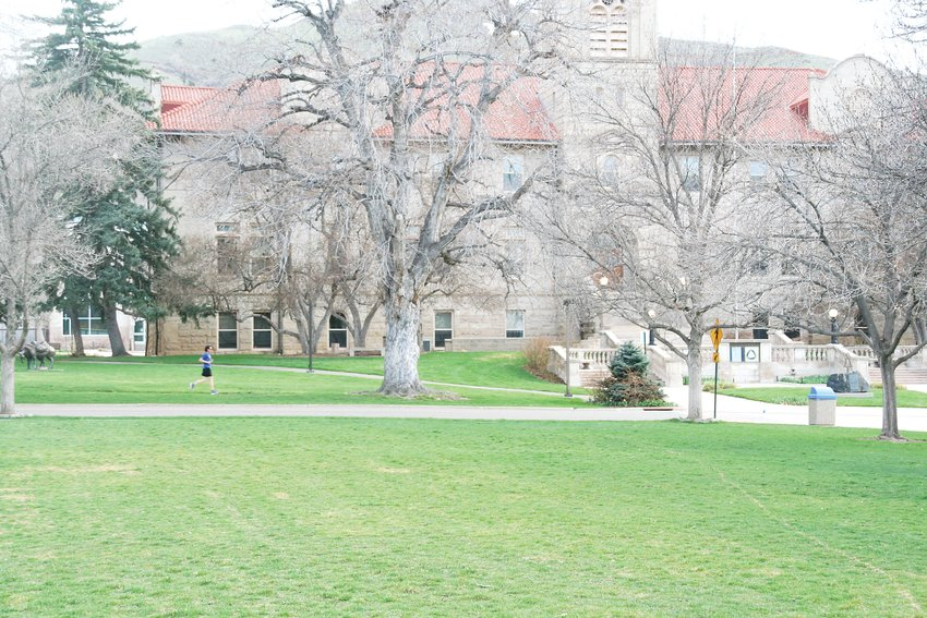 A runner runs on an otherwise empty Colorado School of Mines campus.