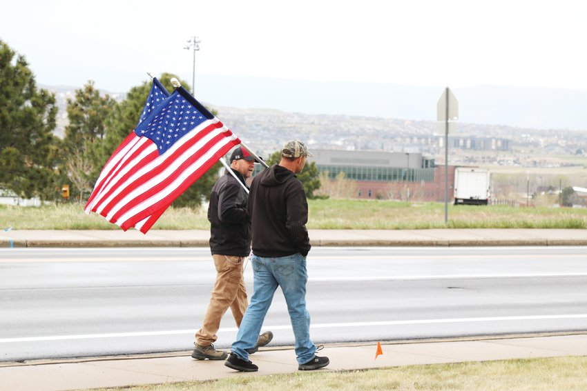 Jed Gilman, left, and John Hulse drove over an hour to Castle Rock May 11 to carry American flags in front of C & C restaurant in support of the business.