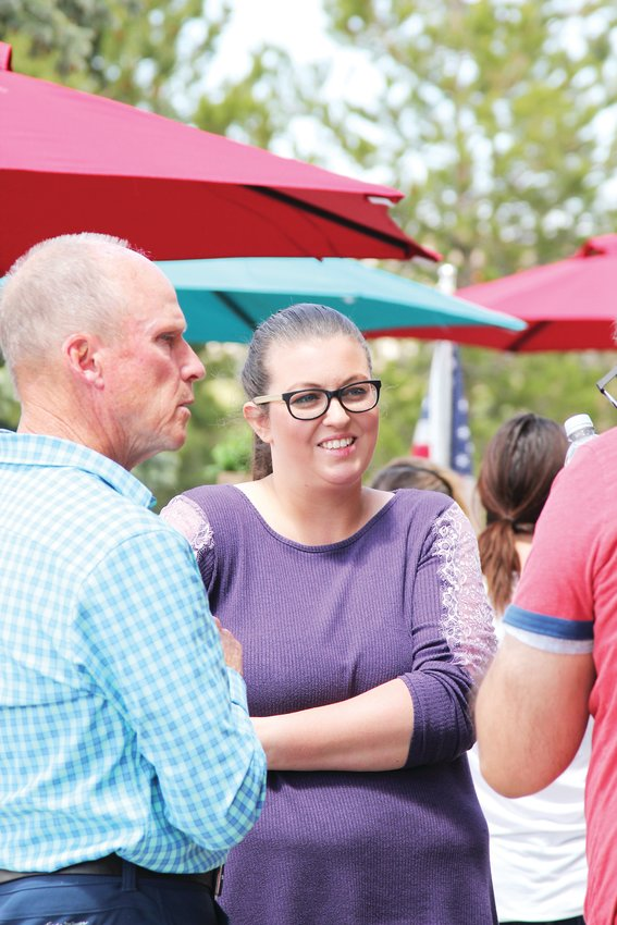 April Arellano, co-owner of C&C Coffee and Kitchen, talks with her husband and guest outside the restaurant on May 12.
