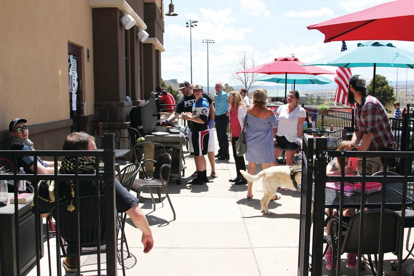 People gathered to the C&C Coffee and Kitchen patio, coming and going for free food on May 12. Few wore masks and more than 10 people socialized during the cookout.