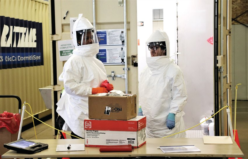 Two workers at the Battelle site in the Adams County Fairgrounds Exhibit Hall prepare to unpack two boxes of used N95 masks, sort them and prepare them to be decontaminated May 14.