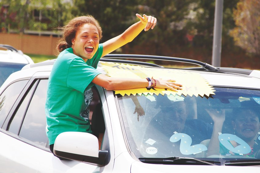 A ThunderRidge High School graduate points and smiles as she sees one of her teachers during a parade of seniors May 15.