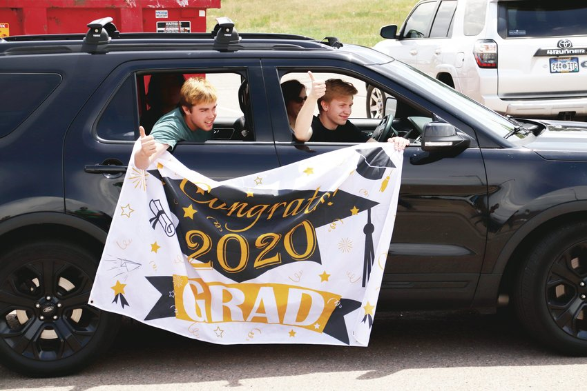"Two boys give thumbs-up after a ThunderRidge High School teacher shouts ""be good"" as they pass by during a May 15 parade of graduates."