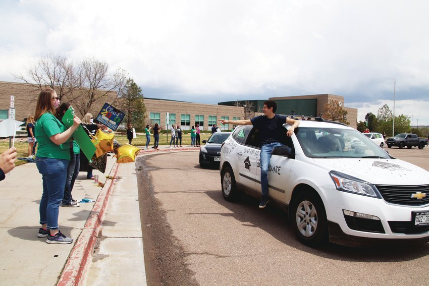 One ThunderRidge High School graduate sits with a leg outside the window while he points at a teacher during a May 15 parade.