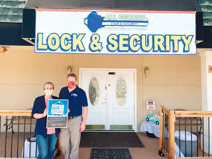 Rita and Ben Lawrence stand outside their business with a poster courtesy of the Safe and Open campaign.