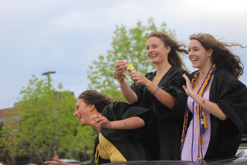 Seniors from Lakewood High School smile as they drive through the school's parking lot. Jeffco Public Schools is aiming to hold graduations in August.