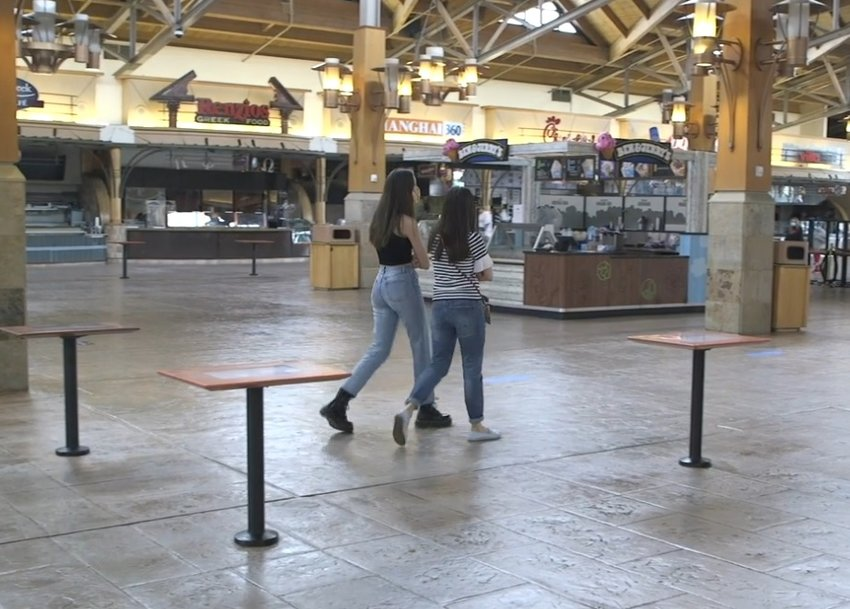 Shoppers stroll through the mostly-empty food court at Park Meadows mall on May 24, 2020.
