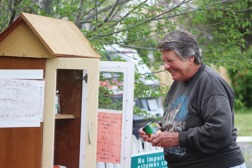 Lakewood resident Bev Noia puts food inside her little free library. Noia has routinely been putting canned food in her little free library outside her house. Food pantries in Jeffco have seen up to 40% of clients coming from new households since the pandemic started.