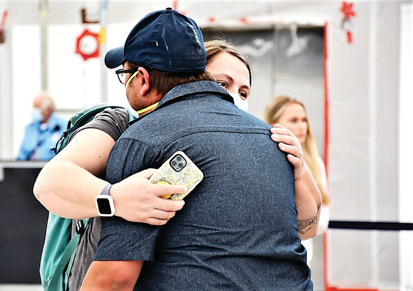 Thornton's Katie Adkins, an emergency room nurse at Westminster's St. Anthony North Regional Medical, hugs her husband Dustin upon arriving back in Denver May 14. Adkins and 33 other Colorado nurses flew to New Jersey to help with that state's COVID-19 response.