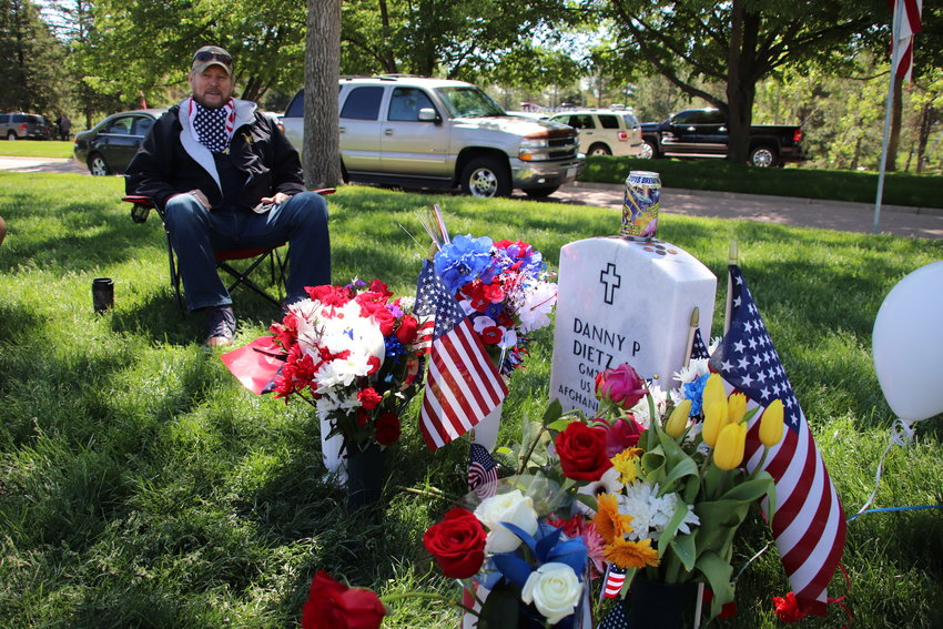 Danny Dietz Sr. sits beside his son's grave at Fort Logan National Cemetery. Dietz Jr., a Navy SEAL, was killed in Afghanistan in 2005.