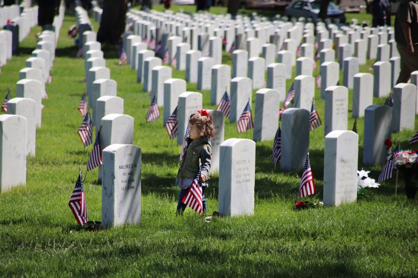 Vivienne Dauro, 1, wanders among the headstones at Fort Logan National Cemetery. Vivenne's dad Michael, a former Navy SEAL, brings his three daughters to the cemetery every year for Memorial Day.
