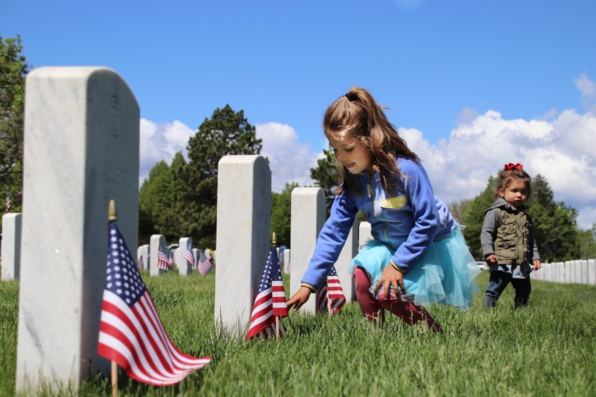 Grace Dauro, 5, lays a rose on a grave at Fort Logan National Cemetery as her sister Vivienne looks on.