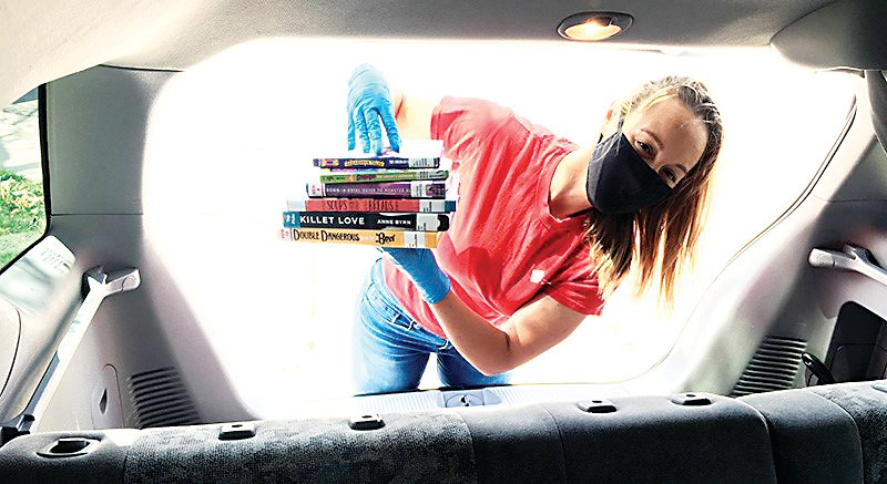 A Jefferson County Public Library staff member outfitted in gloves and a face mask places books in the back of a vehicle.