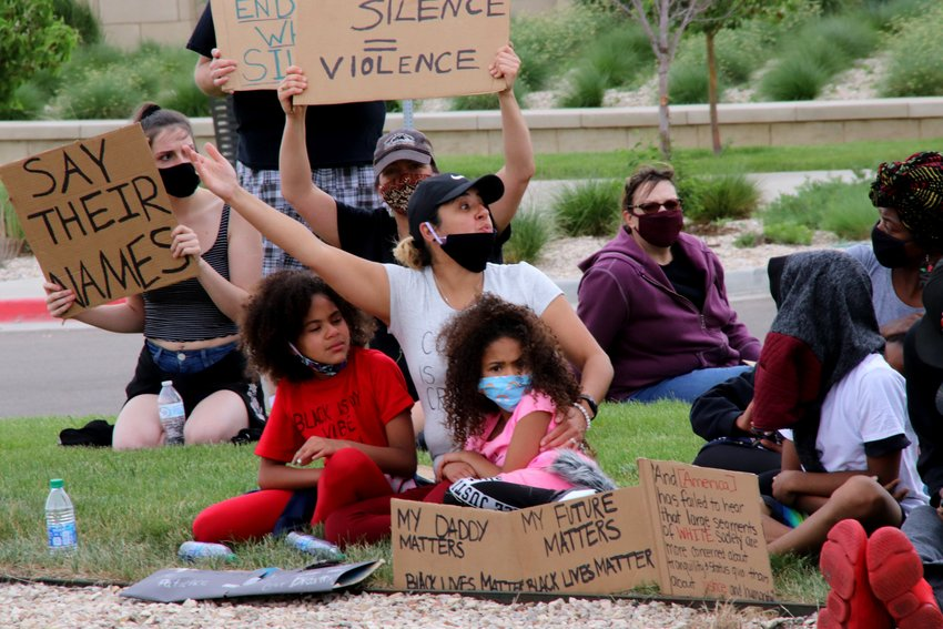 Valerie Carter, sitting with daughters Dominique, on the left, and Dionne, reacts to a heckler June 6 while sitting on the grass in front of the Northglenn Police station on Community Center Drive. The three were part of a group that marched peacefully from E.B. Rains Park to the Justice Center to protest for racial justice.