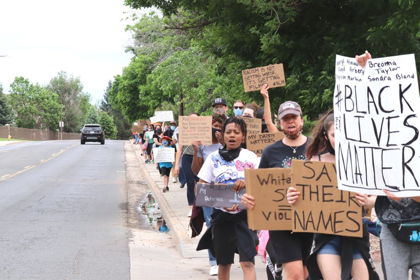 A group of 65 marchers protesting for racial justice walk down Community Center Drive from E.B. Rains Park to the city police department June 6.