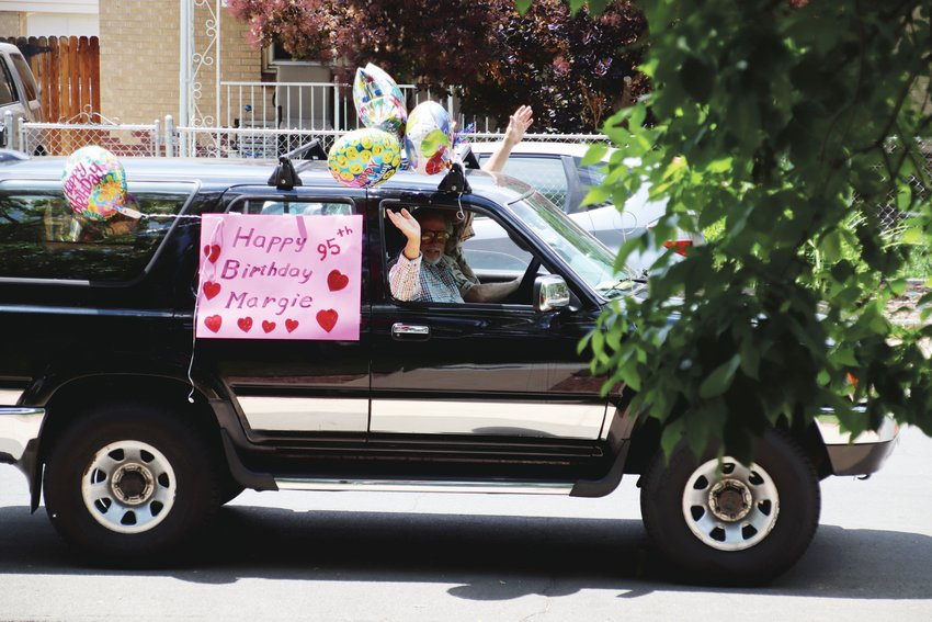 Neighbors Thomas Gardner and Bill Dolzal drive by Margie Ingram's house in a car decked out for Ingram's 95th birthday.