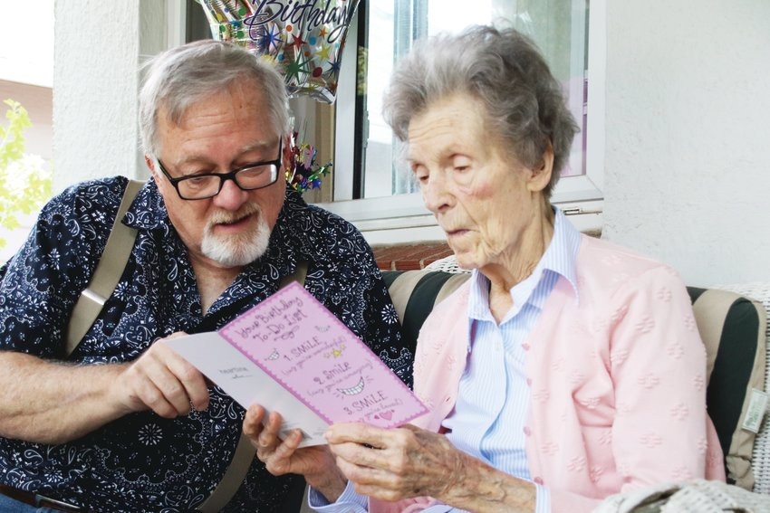 Kerry Ingram, left, reads a birthday card with his mom Margie, who celebrated her birthday with a drive-by party.
