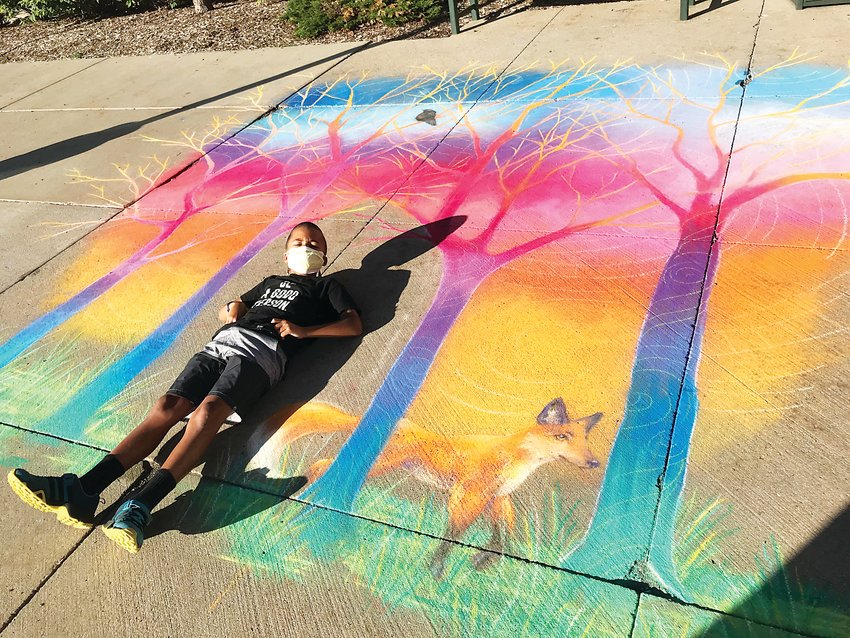 A camper from the city of Wheat Ridge's summer day camp, Sun Camp, poses with artist Olivia McCleod's chalk art piece outside the Wheat Ridge Recreation Center.