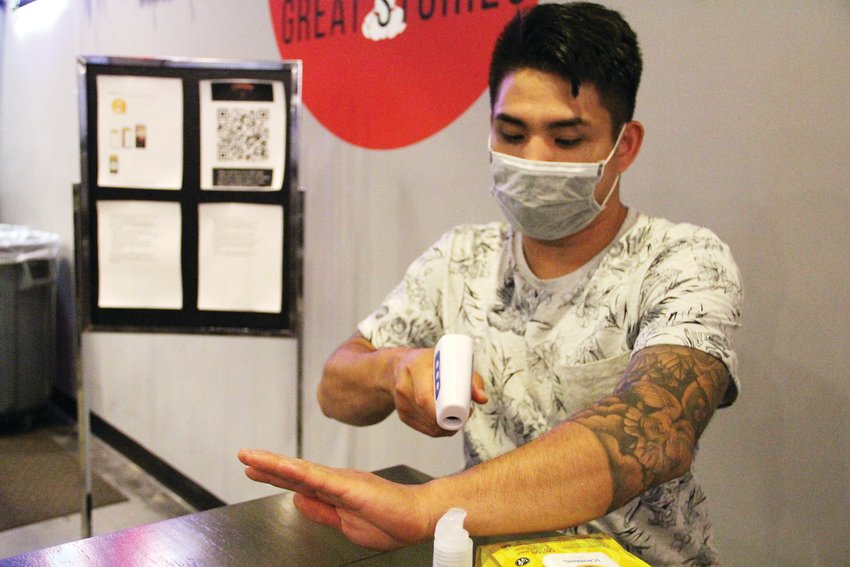 Khiem Nguyen, owner of Crawfish Boil Co. restaurant and bar at The Streets at SouthGlenn, demonstrates on June 4 using a no-contact thermometer — usually, it's pointed at a person's forehead. The tool is one of many supplies the restaurant brought aboard to prevent the spread of COVID-19.
