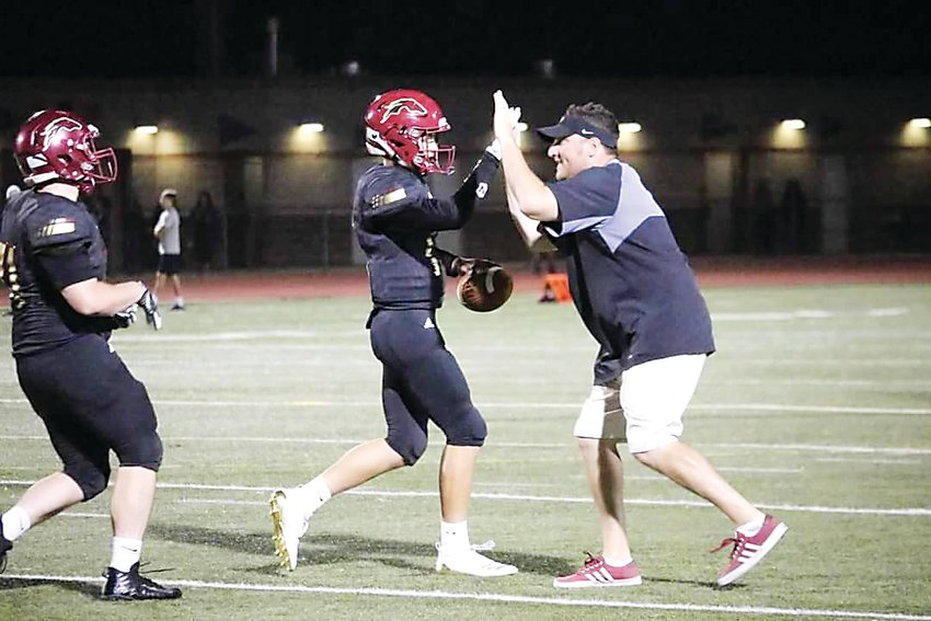 Quarterback Jack Hanenburg greets head coach Jaron Cohen during a game last season. Hanenburg will be a senior and three-year starter for the Mustangs.