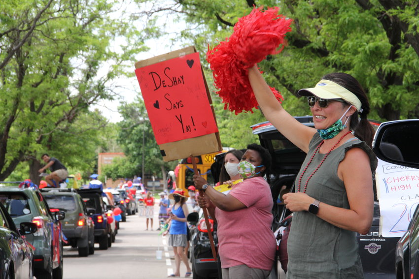 Stephany Shadwell, right, a Cherry Creek High School English teacher, waves a pompom as graduating seniors cruise by June 4 for a drive-thru senior parade. Hundreds of cars rolled through the path — around the perimeter of the campus — for more than two hours.